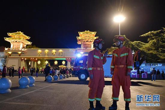 李志亮(左)和队友夜间在兰州市西固区金城公园门前执勤(4月11日摄)。 新华社记者 陈斌 摄