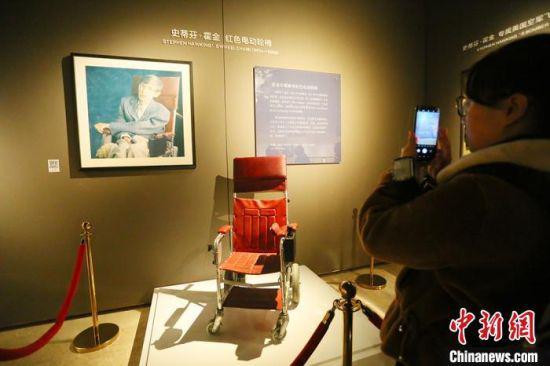 1月16日,参展民众拍照霍金早年乘坐的红色电动轮椅。 高康迪 摄