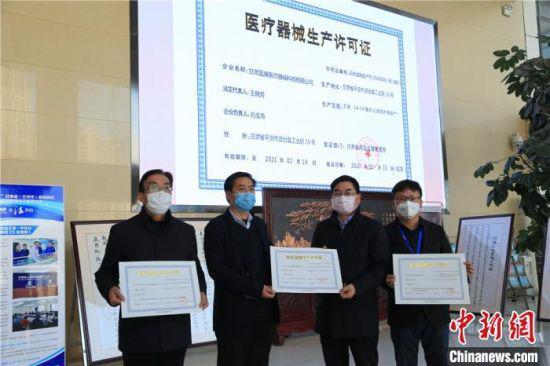 图为甘肃省药品监督管理局副局长王宗伟(右二)为3家防护服生产企业代表发放临时医疗器械注册生产许可证。这意味着,甘肃填补了医用防护用品生产的空白。 史静静 摄