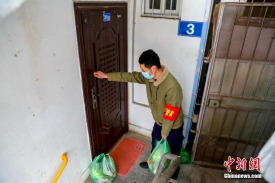 2月10日,武汉市江汉区新华街取水楼社区为辖区的老人送菜上门,社区工作人员把菜放在门口,敲门提醒老人菜已送到。中新社记者 张畅 摄