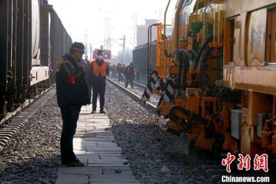 """近日,大型捣固车挥动""""机械手臂""""对兰州北站铁路线路进行精确捣固。 王光辉 摄"""