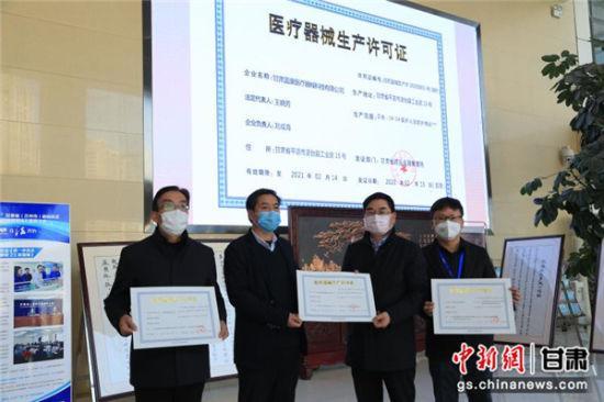 图为2月15日,甘肃省药品监督管理局为3家防护服生产企业代表发放临时医疗器械注册生产许可证。这意味着,甘肃填补了医用防护用品生产的空白。 史静静 摄(资料图)