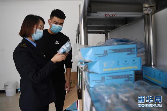 """4月15日,兰州市第二十八中学""""健康副校长""""曹琴(左)与老师一起整理防疫物资。新华社记者 陈斌 摄"""