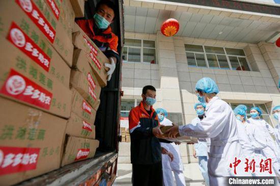 在甘肃省第二人民医院大院内,40多位身穿白大褂的医护人员,取在拼多多拼购的湖北农货快递。 刘勇 摄