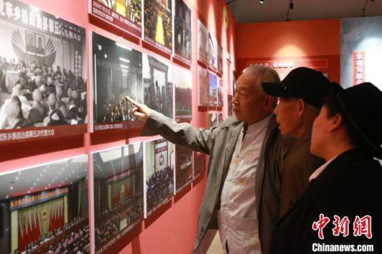 """图为郭庭源(左一)在离开家乡10多年后,以""""退休干部""""身份参观东乡族自治县成立70周年成就展,感慨颇多。"""