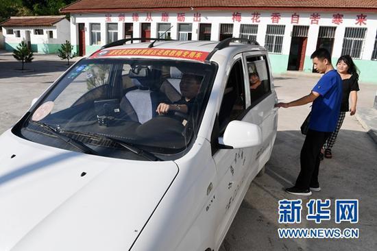"""9月3日,在秦安县陇城教育园区赵山教学点,""""走教""""老师付耀峰(右二)、王昕(右一)准备乘坐教师校车返回园区公寓。"""