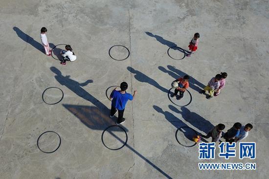 """9月3日,在秦安县陇城教育园区赵山教学点,""""走教""""老师付耀峰(左三)给学生上体育课(无人机照片)。"""
