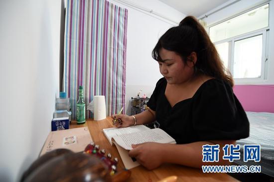 """9月3日,在秦安县陇城教育园区,""""走教""""老师王昕在单身公寓内看书。"""