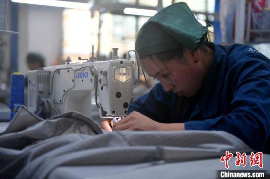 甘肃榕发服装智造公司的工作车间,陈娟娟正在工作中。