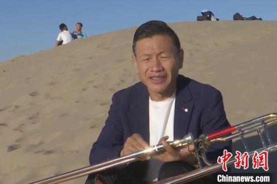 图为王国新带领孩子们在沙漠里演出。 卢武林 摄