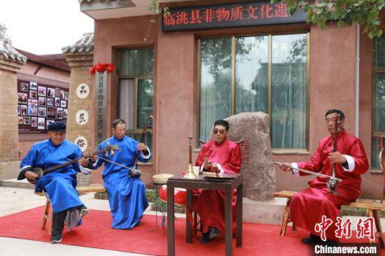 10月12日,甘肃省定西市临洮县举行非物质文化遗产展示中心启动仪式。图为当地皮影戏传承人赵学兵(右二)带领班社表演影子腔。 张婧 摄