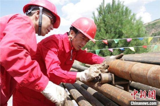 长庆油田第十采油厂井下作业大队高级技师杨义兴(右)和工友正在检查入井工具。(资料图)受访者供图