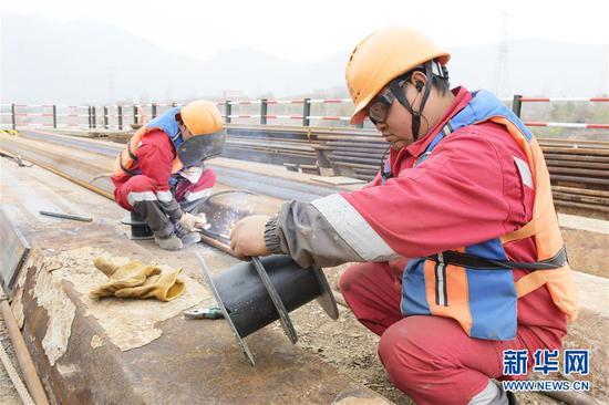 工人在临大高速公路大河家黄河大桥建设现场施工(11月4日摄)。