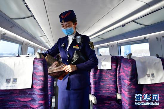 银川客运段列车长董芳在银西高铁运行试验动车组列车上巡检(12月12日摄)。新华社记者 陈斌 摄