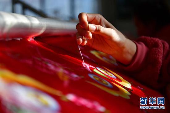 村民在甘肃省庆阳市群英香包有限公司巾帼扶贫车间刺绣(12月14日摄)。新华社记者 陈斌 摄