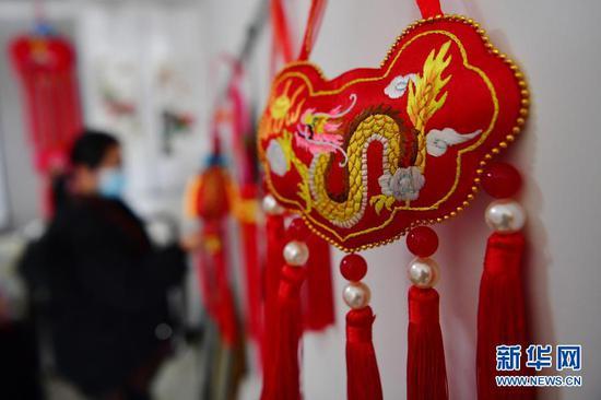 游客在甘肃省庆阳市群英香包有限公司展厅挑选香包(12月14日摄)。新华社记者 陈斌 摄