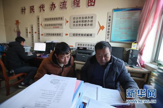 1月5日,在会宁县韩家集镇袁家坪村村委会办公室,任长太(右)和村干部探讨工作。新华社记者 马希平 摄