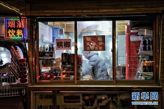 1月7日,在甘肃省兰州市的街边,一位杂货铺的老板正在深夜忙碌。新华网(刘欣瑜 摄)