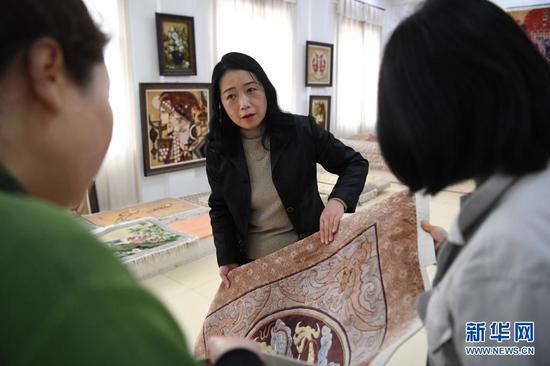 黄晶蓉(中)在天水新天丝毯有限公司的成品展室里和徒弟交流丝毯织造技艺(4月14日摄)。新华社记者 陈斌 摄