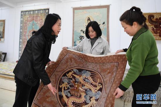 黄晶蓉(左一)在天水新天丝毯有限公司成品展室内和徒弟交流丝毯织造技艺(4月14日摄)。新华社记者 杜哲宇 摄