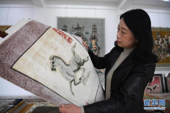 黄晶蓉在天水新天丝毯有限公司的成品展室查看丝毯成品(4月12日摄)。新华社记者 陈斌 摄