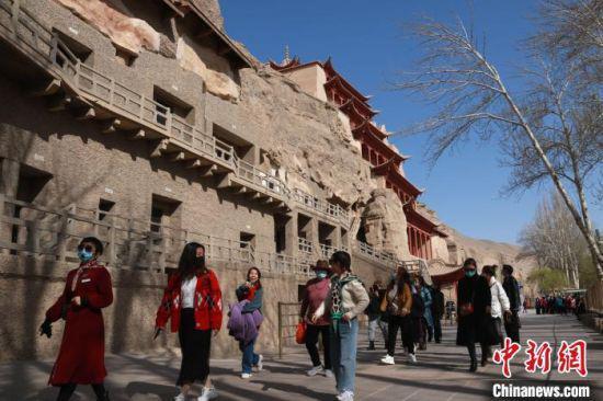 图为4月中旬,游客在敦煌莫高窟参观游玩。 张晓亮 摄