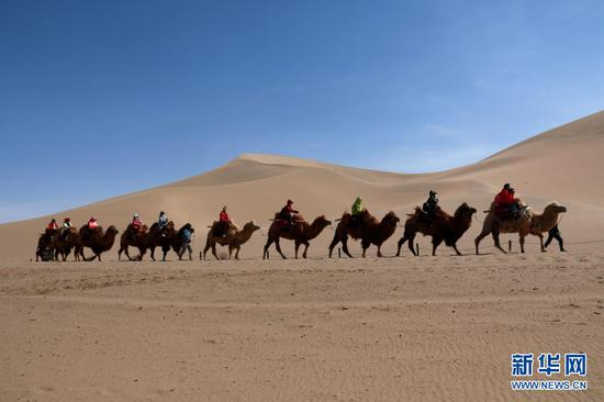 4月25日,游客在甘肃省敦煌市鸣沙山月牙泉景区游览。新华社发(张晓亮 摄)