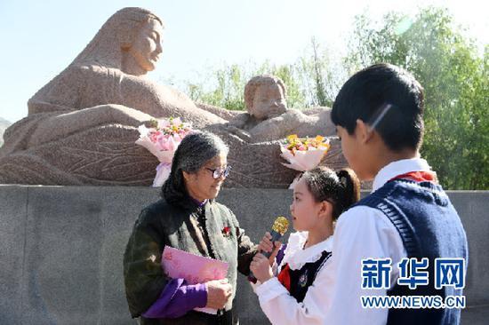 """5月9日,兰州市七里河区学生代表给""""黄河母亲""""创作者何鄂(左一)赠送贺卡。新华社记者 范培珅 摄"""