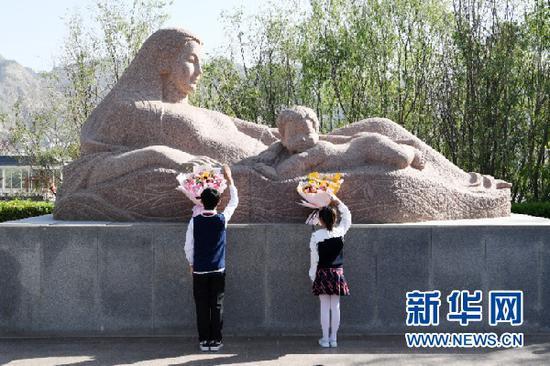 """5月9日,兰州市七里河区学生代表给""""黄河母亲""""献花。新华社记者 范培珅 摄"""