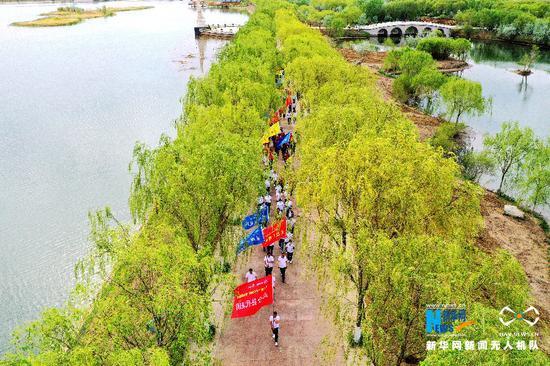 5月10日,健走队伍穿过高台黑河湿地。新华网发 (郑耀德 摄)