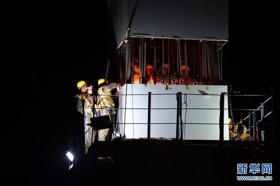 5月14日凌晨,中铁七局路桥公司的工人进行中兰客专甘肃段跨既有线钢横梁吊装施工。新华社记者 陈斌 摄
