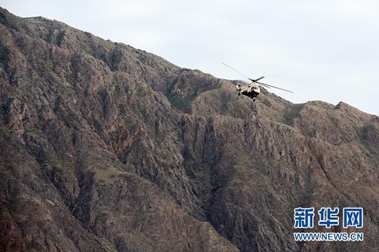 5月23日,直升机在事发区域搜救失联人员。新华社记者 范培珅 摄