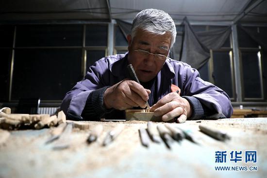 图为团队成员李俊林在雕刻雀替。