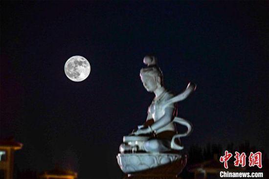 5月26日深夜,一轮超级圆月悬挂在敦煌党河风情线上。(图片为双重曝光)。 王斌银 摄