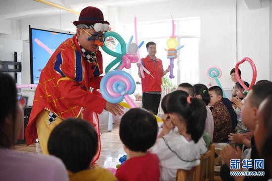 5月27日,中建三局西北公司的志愿者与孩子一起做游戏。新华社记者 陈斌 摄