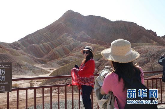 游客在张掖七彩丹霞景区拍照留念。新华社记者 李杰 摄
