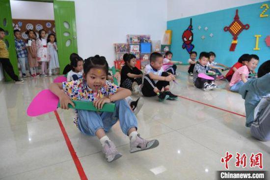 """临近端午节,""""赛龙舟""""、编花绳、包粽子……丰富多彩的趣味活动在甘肃省妇联保育院举行。 杨艳敏 摄"""