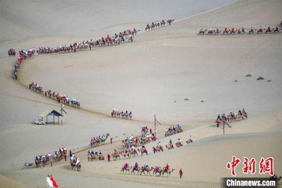 """图为今年端午节假期,丝绸之路国际旅游名城甘肃敦煌鸣沙山出现""""驼队如龙""""景象。 王斌银 摄"""