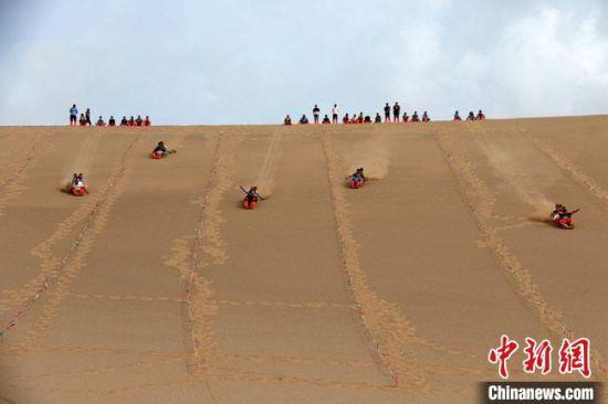 6月13日,敦煌鸣沙山月牙泉景区举办滑沙比赛。 张晓亮 摄