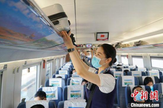 图为中国铁路兰州局集团工作人员在动车组列车上为旅客服务。 苟峰博 摄
