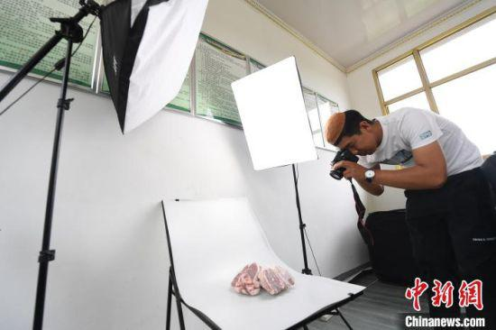 张忠山自学摄影技术,给产品拍照。 杨艳敏 摄