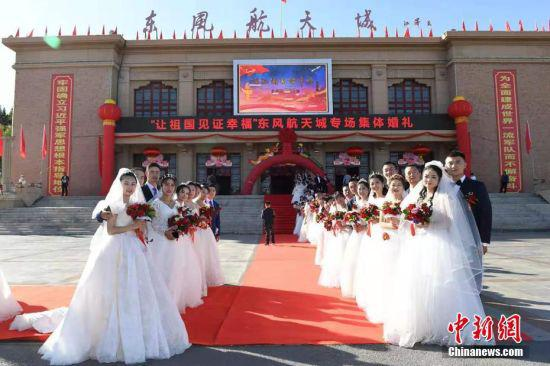 """2019年,以""""让祖国见证幸福""""为主题的专场集体婚礼举行,新人们在酒泉东风航天城前集体合影。 中新社发  汪江波 摄"""