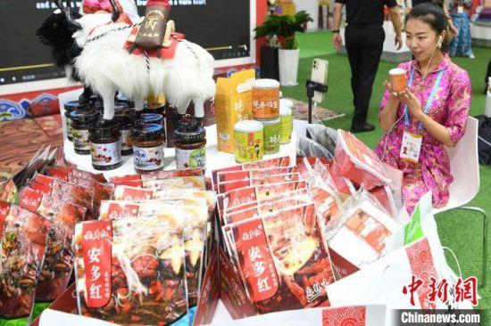 第27届兰洽会展馆内,甘南藏族卓玛现场直播展卖民族特色产品。 杨艳敏 摄