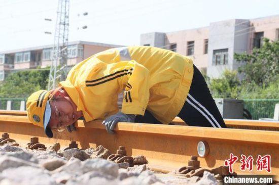"""暴晒在阳光下,她们要趴在50多℃的钢轨上给铁路做""""体检""""。 王光辉 摄"""