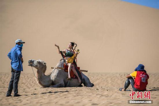 图为游客沙漠中拍照。 王斌银 摄