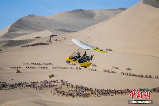 图为游客乘坐滑翔机鸟瞰大漠美景。 王斌银 摄