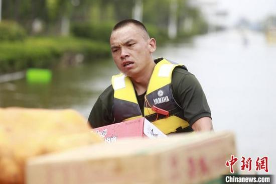 图为贺乐在抗洪一线搬运救灾物资。 霍亚平 摄