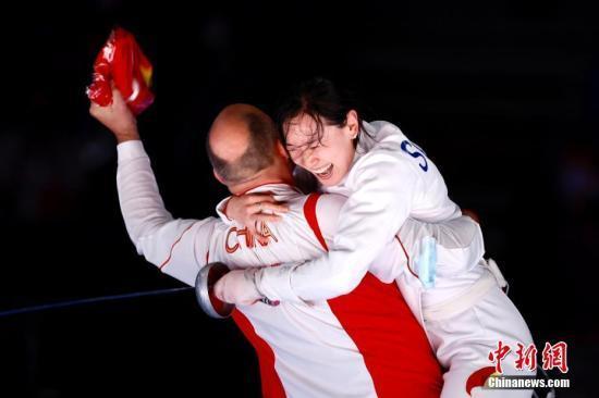 资料图:7月24日晚,东京奥运会女子重剑个人赛结束了决赛的较量,中国选手孙一文以11:10战胜罗马尼亚选手波佩斯库,夺得冠军。图为孙一文夺冠后和团队成员一起庆祝。中新社记者 富田 摄