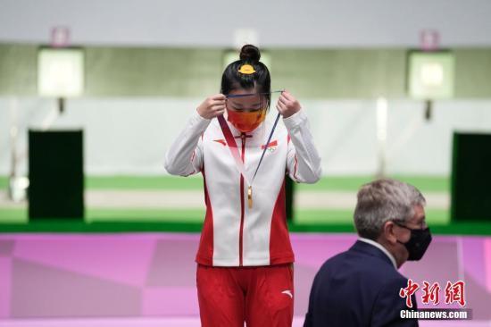 资料图:7月24日举行的东京奥运会女子10米气步枪决赛中,中国选手杨倩夺得冠军,为中国代表团揽入本届奥运会第一枚金牌。这也是本届东京奥运会诞生的首枚金牌。图为杨倩戴上奥运金牌。中新社记者 杜洋 摄