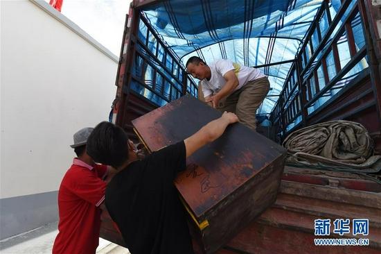 8月7日,在兰州新区,虎吾成(右一)从地质灾害避险搬迁转运车上搬下物品。新华社记者 范培珅 摄